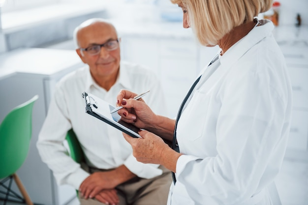 Senior man heeft overleg in de kliniek door de vrouwelijke arts.