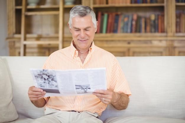 Senior man het lezen van kranten in de woonkamer