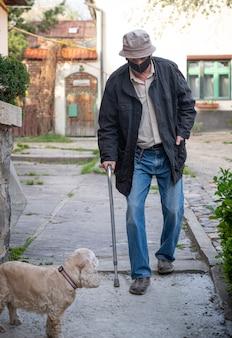 Senior man in beschermend masker met een stok wandelen met een hond in zonnige dag