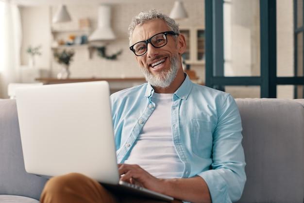 Senior man in casual kleding met laptop en kijkend naar camera met een glimlach terwijl hij thuis op de bank zit