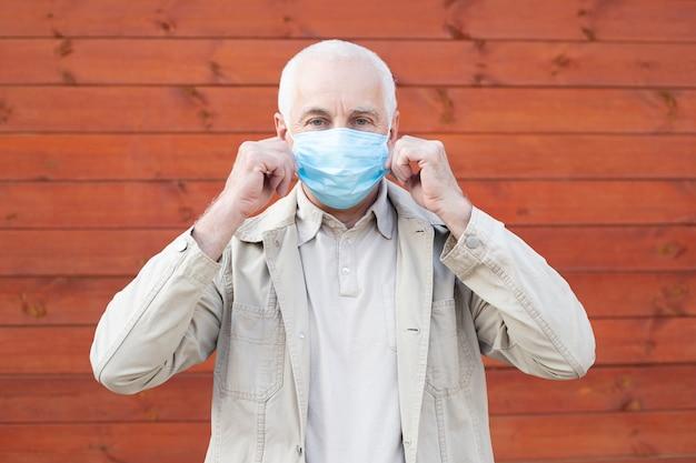 Senior man in een gasmasker om te beschermen tegen infectie met het griepvirus of coronavirus