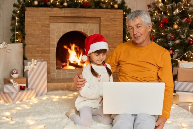 Senior man in geel overhemd zittend op de vloer en laptop bedrijf op knieën, knuffelen zijn kleindochter en kijkt mier camera, schattig kind kijken laptop scherm, jurken kerstmuts.