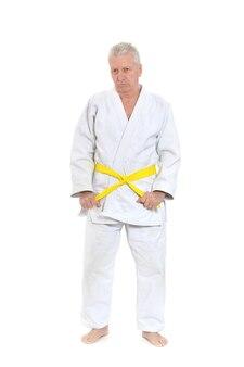 Senior man in karate pose op witte achtergrond