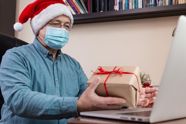 Senior man in kerstman hoed en gezichtsmasker geeft een geschenk en praat met behulp van laptop voor video-oproep vrienden en kinderen. kerst tijdens coronavirus.
