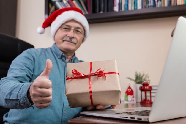 Senior man in kerstman hoed geeft een cadeau en praat met laptop voor video-oproep vrienden en kinderen. kerst tijdens coronavirus.