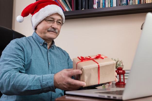 Senior man in kerstman hoed geeft een cadeau en praat met laptop voor video-oproep vrienden en kinderen.