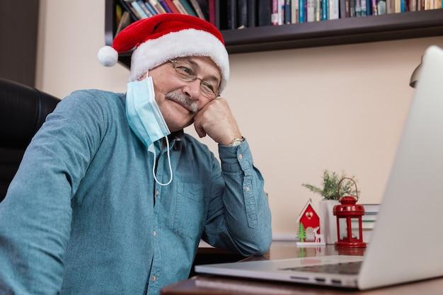 Senior man in kerstman hoed praat met behulp van laptop voor videogesprek vrienden en kinderen. de kamer is feestelijk versierd. kerst tijdens coronavirus.