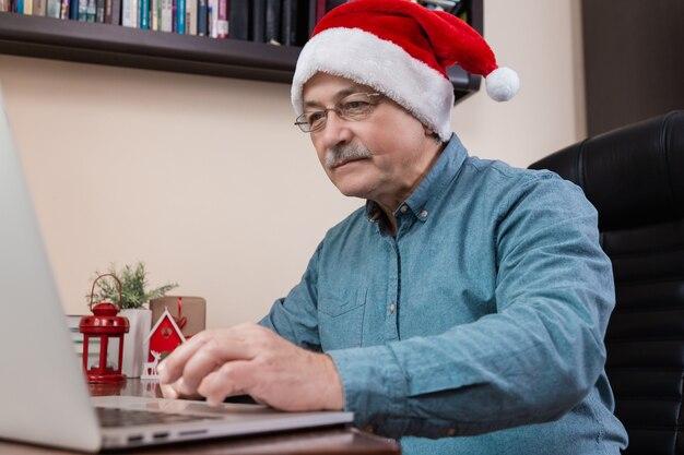 Senior man in kerstman hoed praat met laptop apparaat voor video-oproep vrienden en kinderen. de kamer is feestelijk versierd.