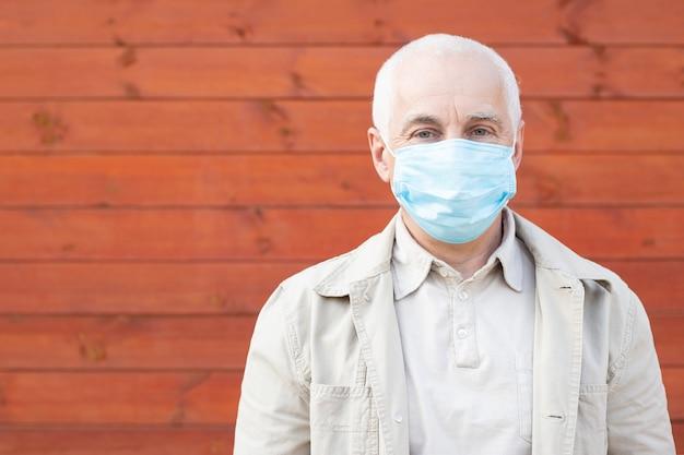 Senior man in masker om te beschermen tegen infectie met griepvirus of coronavirus