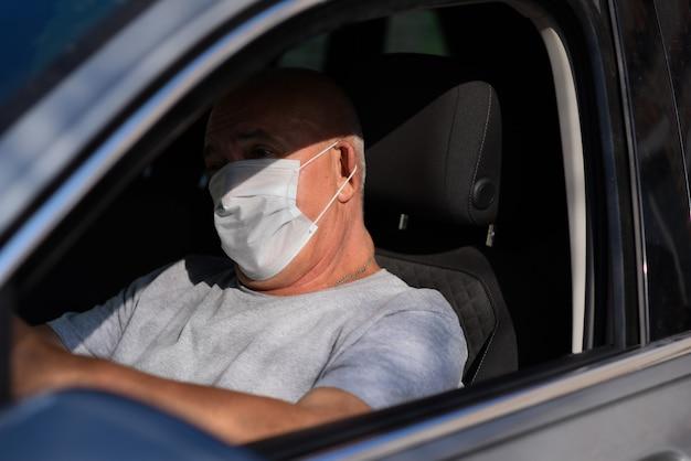 Senior man in medisch masker autorijden, kijkend naar de camera. coronavirus concept.