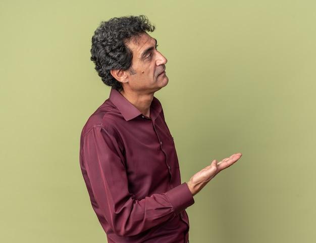 Senior man in paars hemd die opzij kijkt en ontevreden zijn arm opsteekt in ongenoegen en verontwaardiging over groene achtergrond