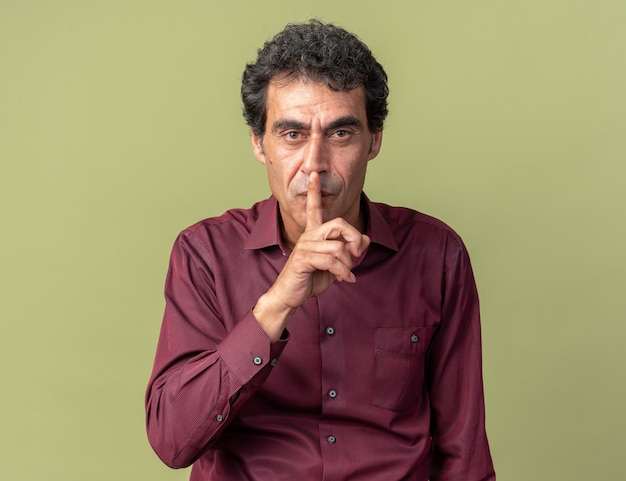 Senior man in paars kijkt naar camera met serieus gezicht en maakt stiltegebaar met vinger op lippen die over groen staan