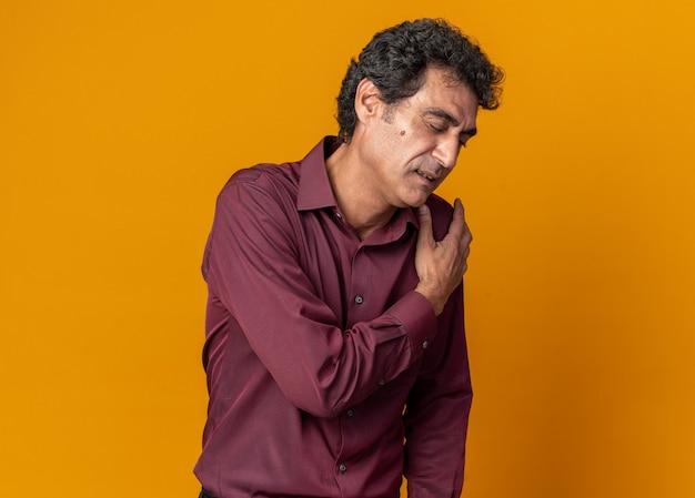 Senior man in paars shirt die er onwel uitziet en zijn schouder aanraakt, voelt pijn terwijl hij over oranje achtergrond staat