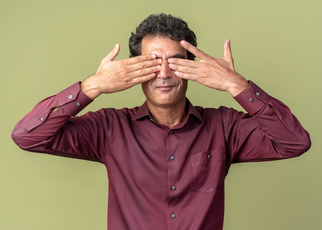 Senior man in paars shirt die ogen bedekt met handen die over groene achtergrond staan