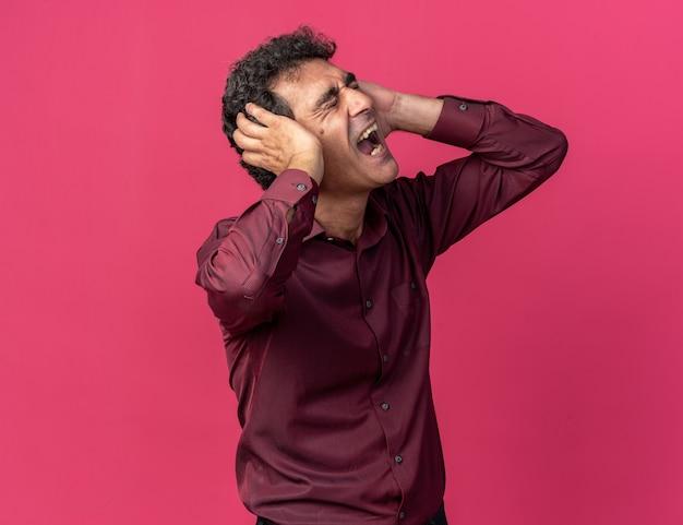 Senior man in paars shirt die oren bedekt met handen schreeuwend met geërgerde uitdrukking