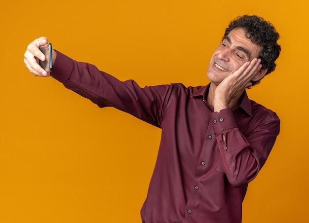Senior man in paars shirt doet selfie met smartphone glimlachend zelfverzekerd over oranje