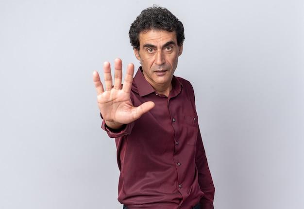 Senior man in paars shirt kijken camera met ernstig gezicht maken stopgebaar met hand staande op witte achtergrond