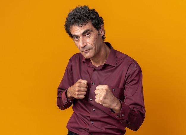 Senior man in paars shirt kijken camera met gebalde vuisten poseren als een bokser die zelfverzekerd over een oranje achtergrond staat