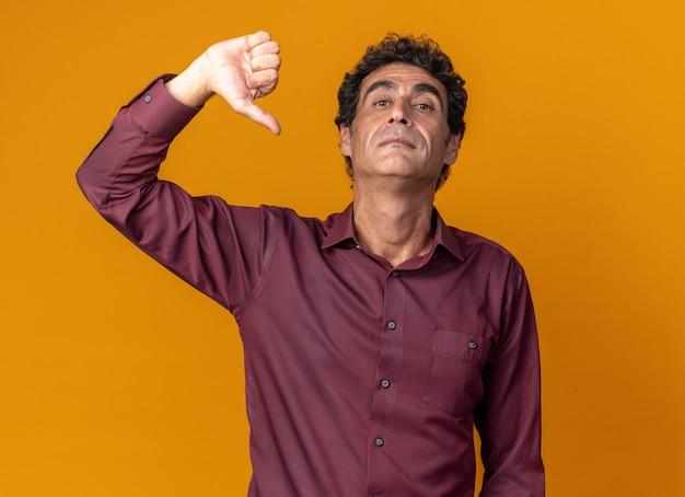 Senior man in paars shirt kijken camera met serieus gezicht met duimen naar beneden staande over oranje