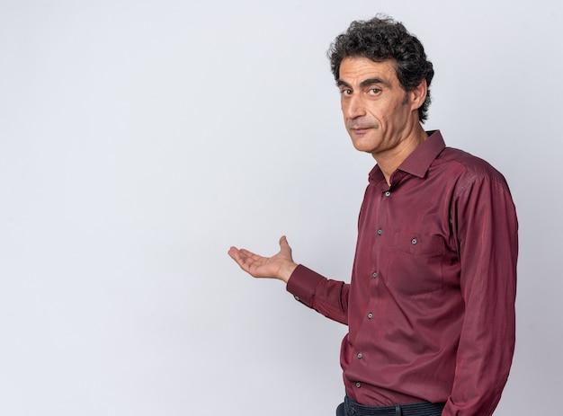Senior man in paars shirt kijken camera met serieus gezicht presenteren kopie ruimte met arm van zijn hand staande op witte achtergrond