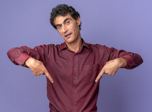 Senior man in paars shirt kijken camera met serieus gezicht wijzend met wijsvingers naar beneden staande over blauwe achtergrond