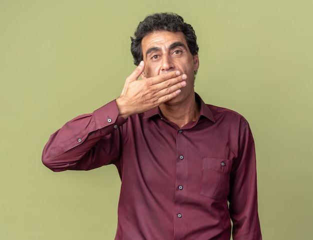 Senior man in paars shirt kijkend naar camera die geschokt is en mond bedekt met hand die over groene achtergrond staat