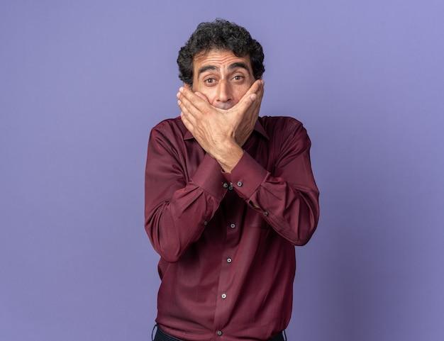 Senior man in paars shirt kijkend naar camera die geschokt is en mond bedekt met handen die over blauwe achtergrond staan