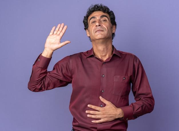 Senior man in paars shirt kijkend naar camera die hand opsteekt en er zelfverzekerd uitziet