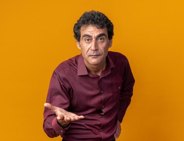 Senior man in paars shirt kijkend naar camera met arm uit alsof hij een vraag stelt over oranje standing