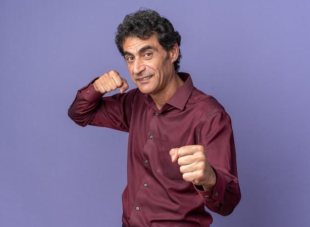Senior man in paars shirt kijkend naar camera met gebalde vuisten die zich voordeed als een bokser die blij en opgewekt over blauw staat