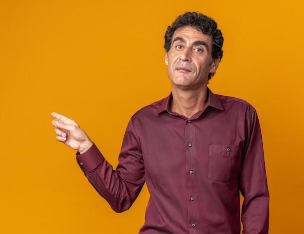 Senior man in paars shirt kijkend naar camera met serieus gezicht wijzend met wijsvinger naar de zijkant