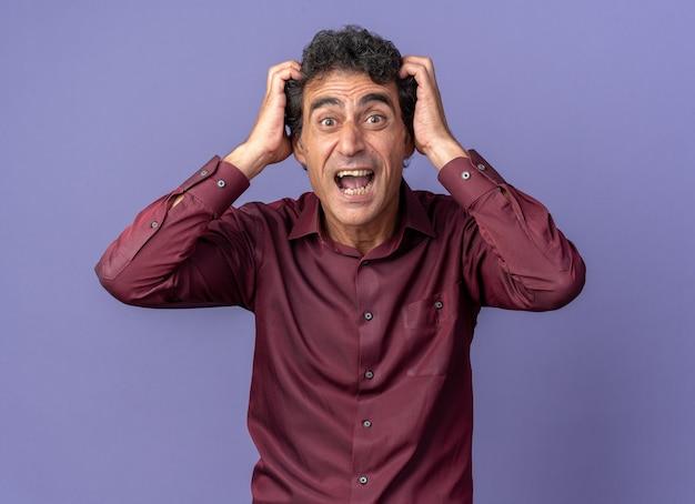Senior man in paars shirt kijkend naar camera schreeuwend en trekkend aan zijn haar dat wild over blauwe achtergrond staat