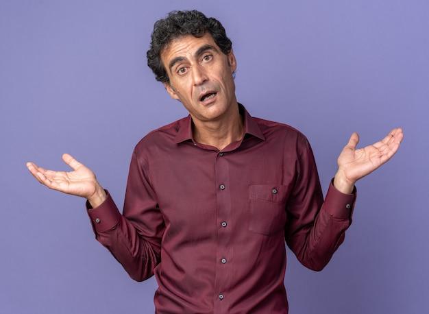 Senior man in paars shirt kijkend naar camera verward schouders ophalend zonder antwoord over blauwe achtergrond