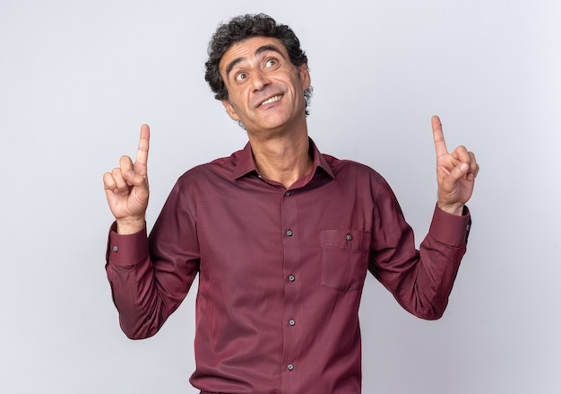 Senior man in paars shirt kijkt blij en verrast op en wijst met wijsvingers omhoog over een witte achtergrond