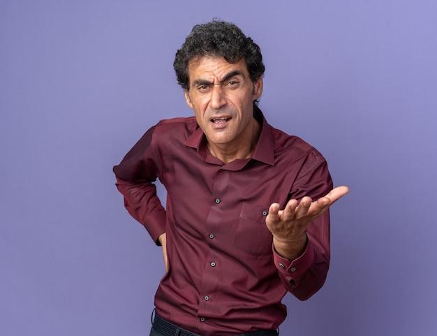 Senior man in paars shirt kijkt naar camera met boos gezicht dat arm opheft als ruzie of vraag stellen