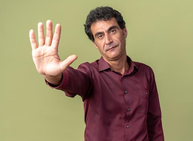 Senior man in paars shirt kijkt naar camera met serieus gezicht en maakt stopgebaar met open hand die over groene achtergrond staat