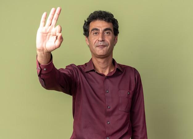 Senior man in paars shirt kijkt naar camera met serieuze zelfverzekerde uitdrukking die een ok teken laat zien dat over groene achtergrond staat