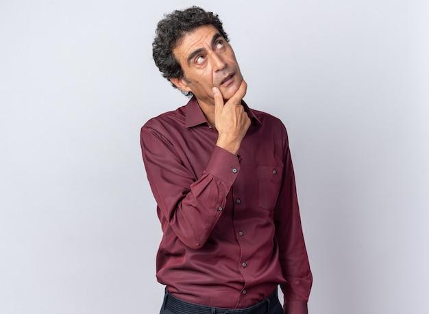 Senior man in paars shirt kijkt omhoog met de hand op de kin, verbaasd over wit