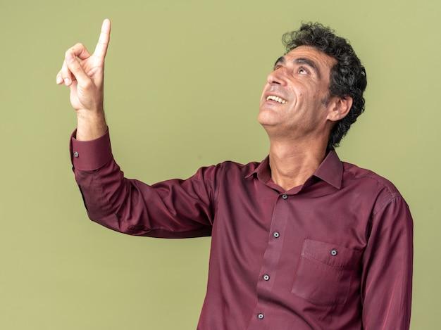 Senior man in paars shirt kijkt omhoog met smle op gezicht wijzend met wijsvinger omhoog staande over groen