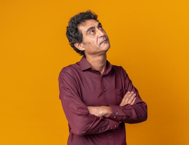Senior man in paars shirt kijkt op met serieus gezicht verbaasd met gekruiste armen over oranje achtergrond