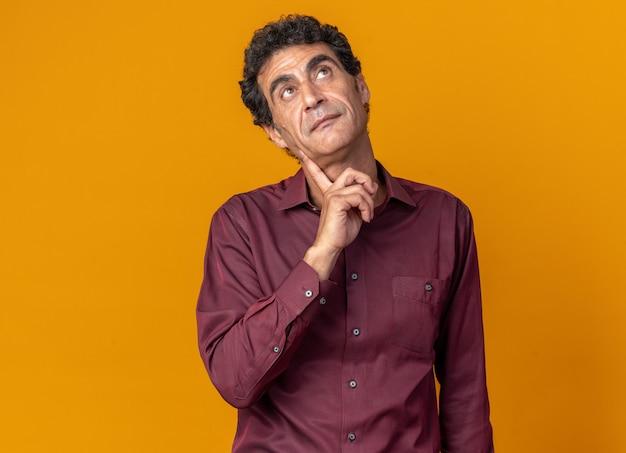 Senior man in paars shirt kijkt verbaasd omhoog terwijl hij over oranje achtergrond staat