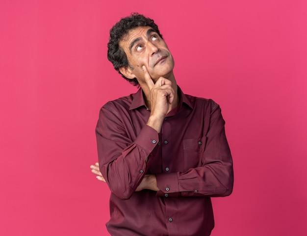 Senior man in paars shirt kijkt verbaasd omhoog terwijl hij over roze staat