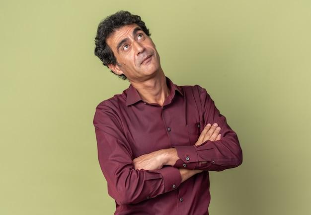 Senior man in paars shirt kijkt verbaasd op met gekruiste armen over groene achtergrond