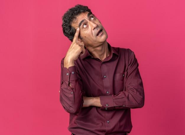 Senior man in paars shirt kijkt verbaasd op terwijl hij zijn hoofd krabt terwijl hij over roze achtergrond staat