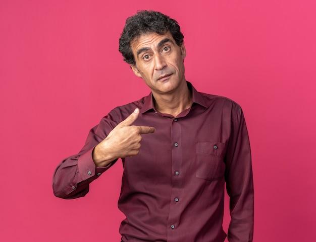 Senior man in paars shirt kijkt verward naar camera en wijst naar zichzelf terwijl hij over roze achtergrond staat