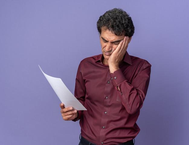 Senior man in paars shirt met blanco pagina die ernaar kijkt met een verwarde uitdrukking die over blauw staat