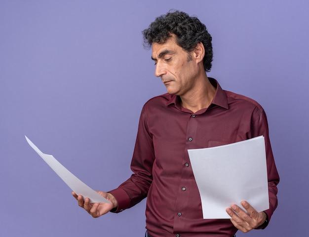 Senior man in paars shirt met blanco pagina's die er verward uitziet en twijfels heeft over blauw