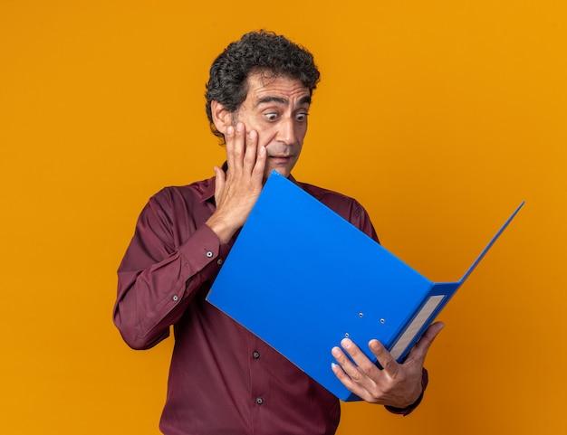 Senior man in paars shirt met blauwe map die er verbaasd en verrast naar kijkt terwijl hij over oranje staat