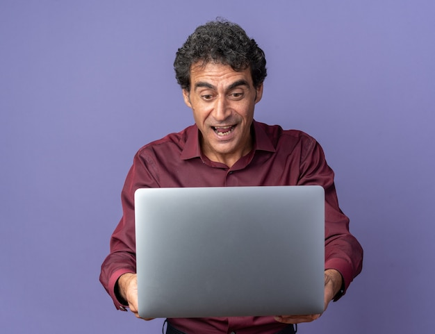 Senior man in paars shirt met laptop die er verbaasd en verrast naar kijkt