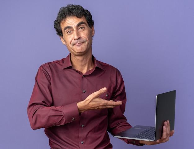 Senior man in paars shirt met laptop die het presenteert met een arm van de hand die zelfverzekerd glimlacht en over een blauwe achtergrond staat